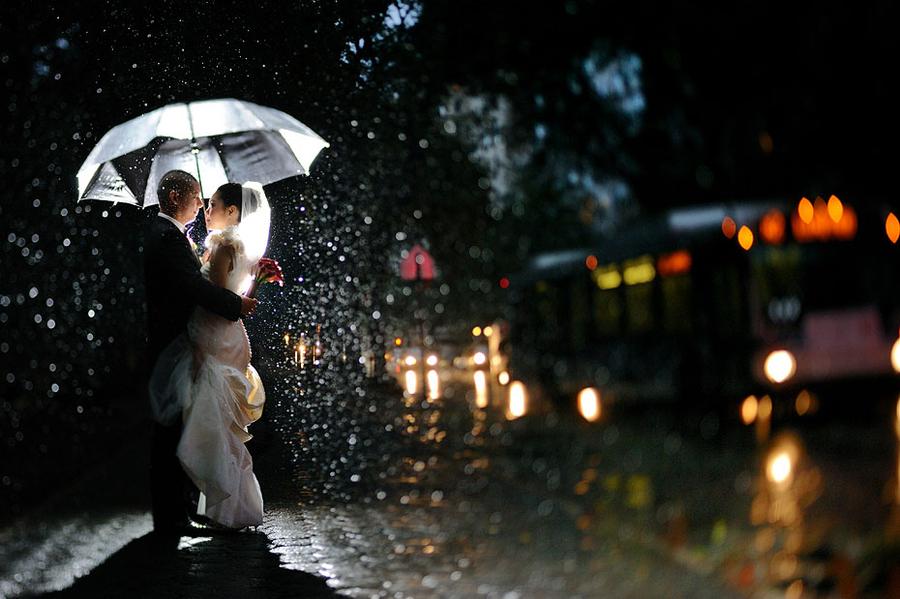 Couple under an umbrella at night