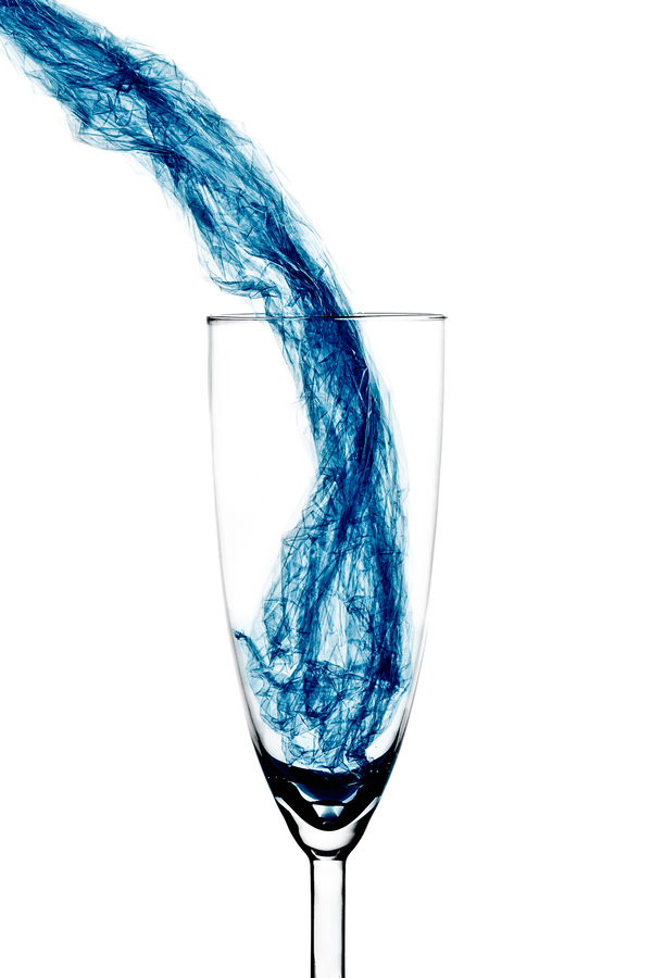blue water pouring into a glass
