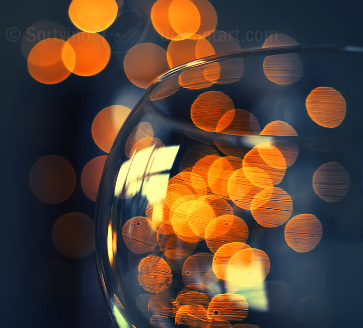 Orange bokeh behind wine glass