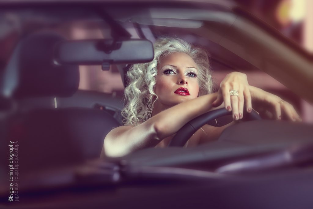 fashion photography by evgeny lanin. A model sitting inside a car
